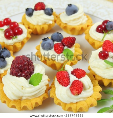 Fresh delicious fruit tarts with cream and berries on a plate