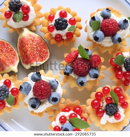 Fresh delicious fruit tarts with cream and berries on a plate - stock photo