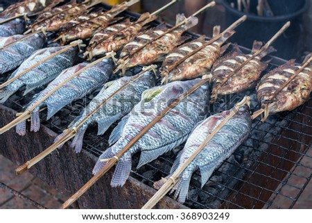 fresh delicious grilled fish, tilapia, nile fish with salt at market, fish salty grill closeup of delicious grilled seafood - stock photo