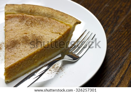 Fresh delicious home made creamy pumpkin pie on white plate on rustic wooden surface. - stock photo