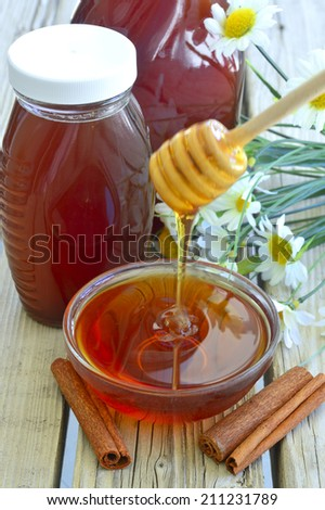 Fresh delicious honey in a bowl on the table near the cinnamon. - stock photo