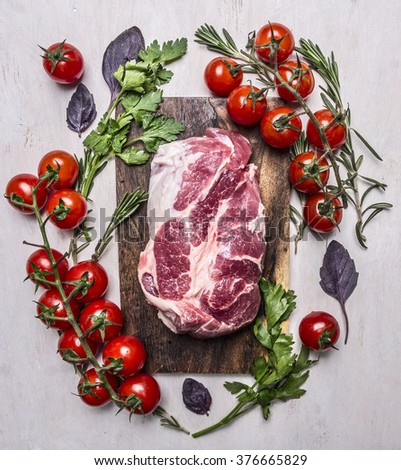 fresh, delicious raw pork steak on a cutting board with vegetables, herbs on wooden rustic background top view close up - stock photo