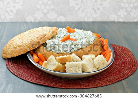Fresh, delicious spinach dip in a round loaf of bread with bread cubes and carrots for dipping. - stock photo