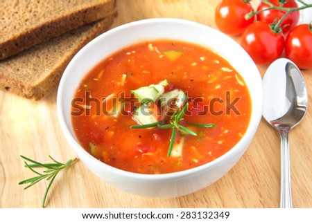 Fresh delicious tasty cold tomato soup gazpacho in white bowl with spoon on wooden board, closeup, horizontal - stock photo