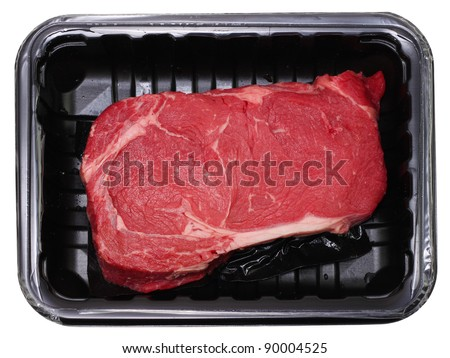 Fresh delmonico or rib eye steak isolated on white in black package - stock photo