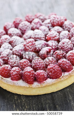 Fresh dessert fruit tart covered in raspberries