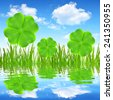Fresh dewy green grass with clover leaf reflecting on the water surface. - stock photo