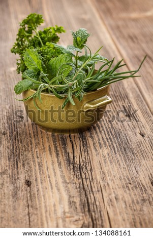 Fresh different herbs in green bowl - stock photo