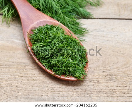 Fresh dill in a wooden spoon. Macro with shallow dof. - stock photo