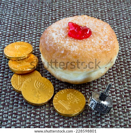 Fresh donut with jam, silver dreidel and chocolate coins for Hanukkah celebration. - stock photo