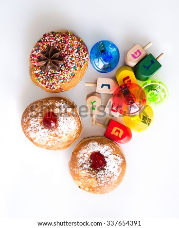 Fresh donuts and colorful dreidels for Hanuka  Jewish Holiday. View from above. - stock photo