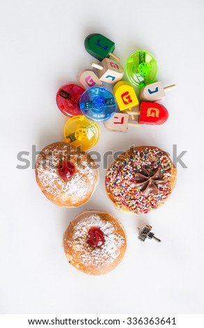 Fresh donuts and colorful  dreidels  for Hanukkah Jewish Holiday. View from above. - stock photo