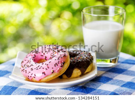Fresh donuts and glass of milk on nature background. - stock photo
