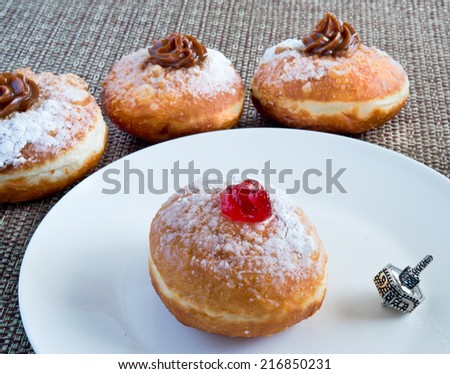 Fresh donuts and silver dreidel for Hanukkah celebration. - stock photo