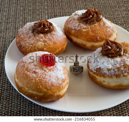 Fresh donuts and silver dreidel on white plate for Hanukkah celebration. - stock photo