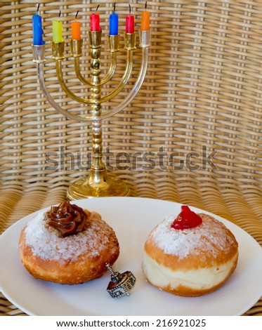 Fresh donuts and silver dreidel over menorah with candles for Hanukkah celebration. - stock photo
