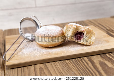 """Fresh donuts with icing sugar and jam with sign """"donuts"""" on wooden table - stock photo"""
