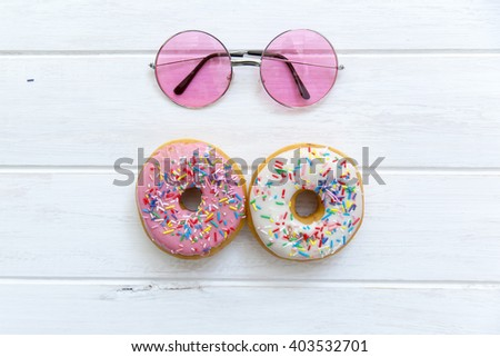 Fresh donuts with sunglasses on white rustic table - stock photo