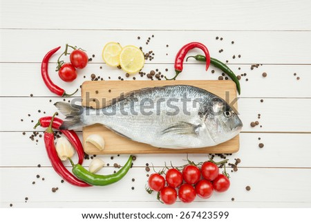 Fresh dorado fish with lemon on wooden cutting board - stock photo