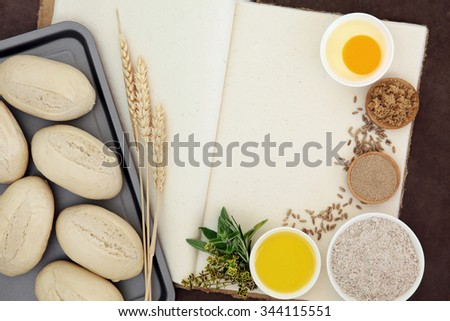 Fresh dough bread rolls with baking ingredients, wheat sheaths and herbs on old hemp notebook over lokta background. - stock photo