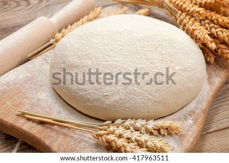Fresh dough on a board with ears of wheat and rolling pin.