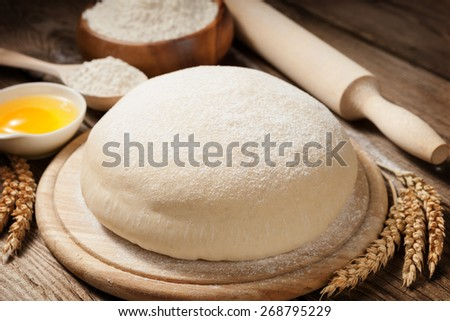 Fresh dough on the old board. rural still life - stock photo