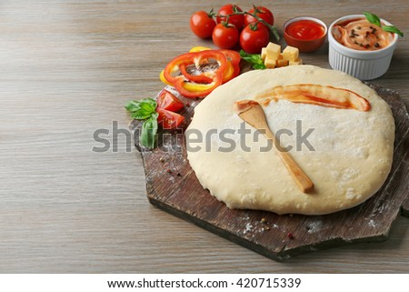 Fresh dough prepared for pizza with tomatoes and sliced pepper on a wooden board, close up - stock photo