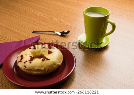 fresh doughnut on a marsala plate and coffee on table - stock photo