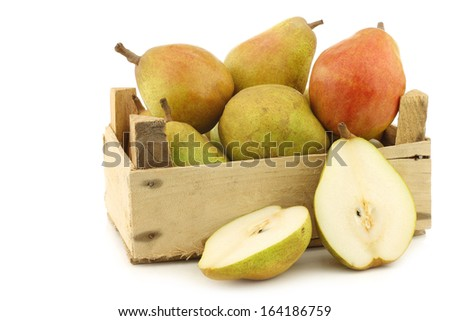 """fresh """"doyenne de comice"""" pears and a cut one in a wooden crate on a white background  - stock photo"""