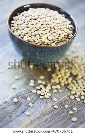 Fresh dried green lentils in ceramic bowl set on wooden table