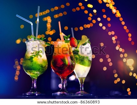 Fresh drink coctails, green mint and lime on a color background blur bokeh - stock photo