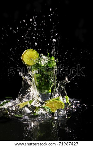 Fresh drink with splashesh of water, green mint and lime on black background - stock photo