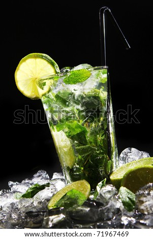 Fresh drink with splashesh of water, green mint and lime on black background