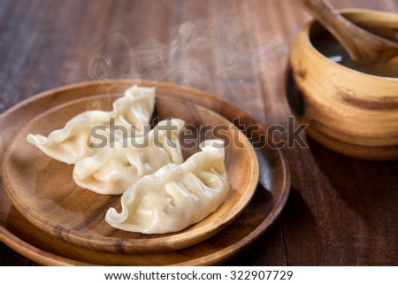 Fresh dumplings with hot steams on wood plate with soup. Popular Chinese dish on rustic old vintage wooden background.  - stock photo