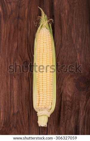 Fresh ear of corn on a brown wooden background - stock photo