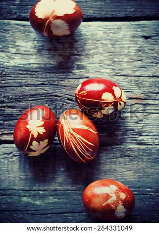 Fresh Easter Bio Eggs on Wooden Table Decorated with Natural Fresh Leaves and Boiled in Onions Peels. Toned - stock photo