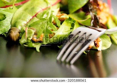 Fresh ecological salad mix with nuts on black plate, macro