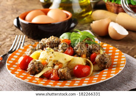 Fresh egg pasta with cherry tomatoes and meatballs on complex background