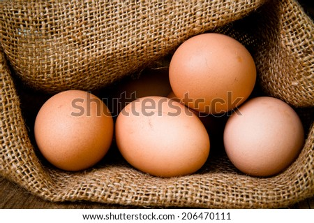 Fresh Egg With Burlap Sack Harvest on Wooden Table Background, Food Rustic Still Life Style. Concept and Idea for Homemade Food Art Decoration.