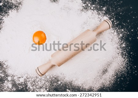 Fresh Egg yolk  and rolling pin on flour on black background - stock photo