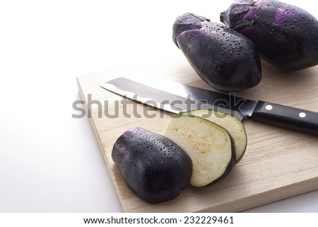 fresh eggplants cut on the chopping board with knife - stock photo