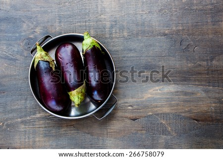 Fresh eggplants on dark wooden background.. Vegetarian food, health or cooking concept. - stock photo
