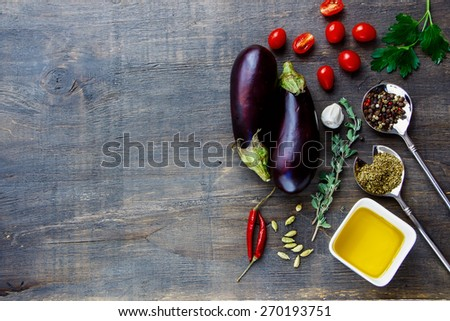 Fresh eggplants with aromatic herbs, spices and vegetables on a Wooden Background. Vegetarian food, health or cooking concept. - stock photo