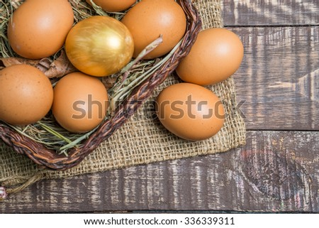Fresh eggs and golden egg on wood vintage background  - stock photo