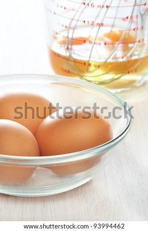 Fresh eggs in a glass bowl and metal whisk with a raw egg in a measuring cup