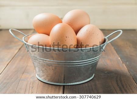 Fresh eggs in aluminium bucket on wood background - stock photo