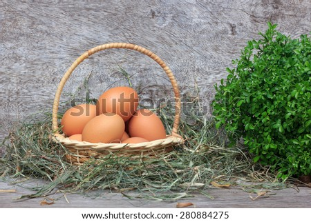 Fresh eggs in wood basket on wooden