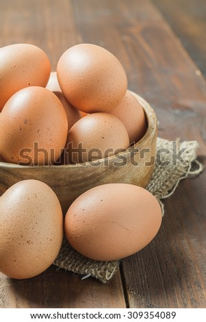 Fresh eggs in wood bowl on wood background