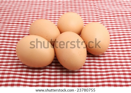 fresh eggs on red table