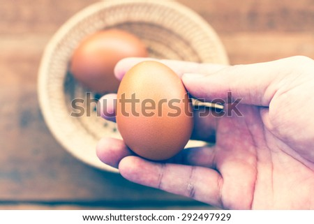 Fresh eggs on the wooden table and have people come to collect the eggs to cook and color reproduction vintage portrait or older. - stock photo